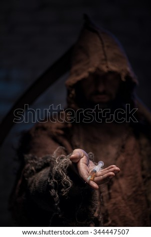 Grim Reaper is holding a syringe of narcotic and proposing it. He is standing with a scythe and looking forward with anticipation - stock photo
