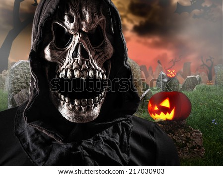 Grim reaper on graveyard, Halloween background. - stock photo
