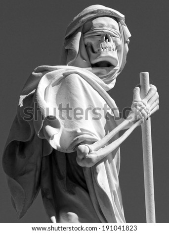 grim reaper statue on cemetery - stock photo