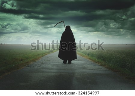 Grim reaper walking on a dark desolate road .Halloween and death - stock photo