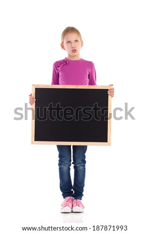 Grimacing schoolgirl standing with blackboard. Full length studio shot isolated on white. - stock photo