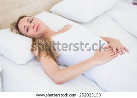 Grimacing woman suffering with stomach pain at home in the bedroom - stock photo