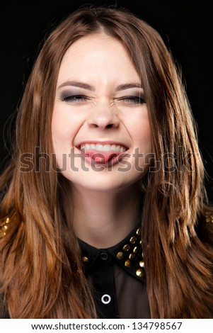 Grimacing young woman making silly face sticking out her tongue on black background - stock photo