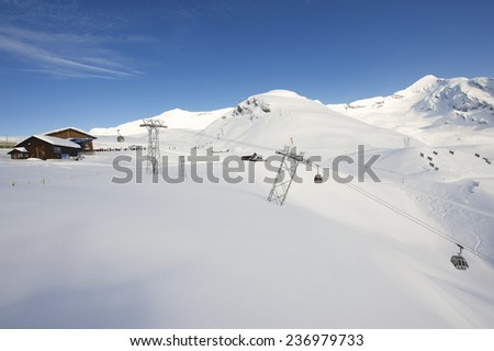 GRINDELWALD, SWITZERLAND - MARCH 07, 2009: Cable car gondolas move skiers uphill at the ski resort on March 07, 2009 in Grindelwald, Switzerland.  - stock photo