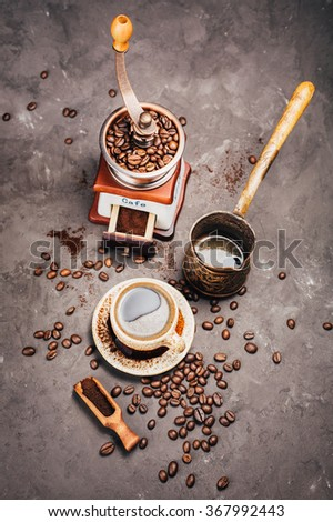 Grinder, cezve,  and a cup of freshly brewed coffee on a dark background - stock photo