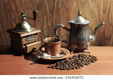 Grinder, cup of coffee, beans and coffee pot - stock photo