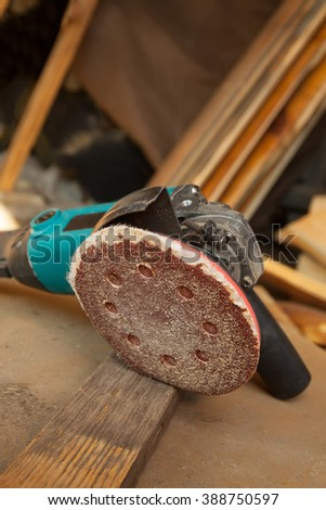 Grinder on the job on old wooden workbench - stock photo