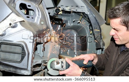 Grinding after welding work at a car. - stock photo