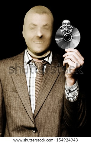 Grinning business man wearing a stocking mask to hide his features holds up a DVD with a skull and crossbones, conceptual of pirating and copyright theft - stock photo
