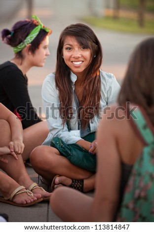 Grinning Filipino girl with friends sitting cross legged - stock photo