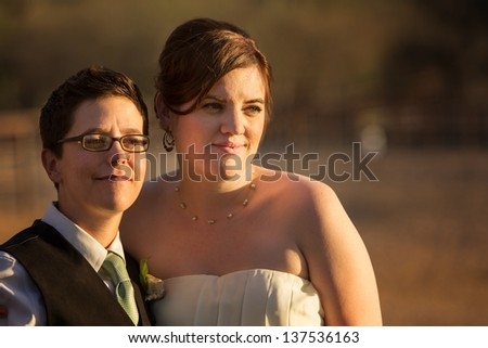 Grinning gay married couple outside after wedding - stock photo