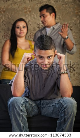 Grinning Hispanic teenager plugging his ears with frustrated parents - stock photo