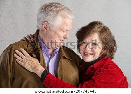 Grinning senior husband looking at his smiling wife - stock photo