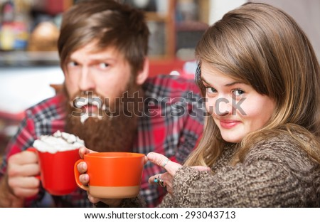 Grinning woman pointing to clueless man with cream on his beard - stock photo
