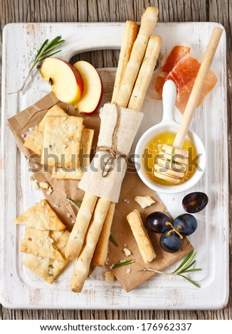 Grissini bread sticks, crackers with salt, rosemary honey, prosciutto ham, apple and grape on a white cooking board. - stock photo
