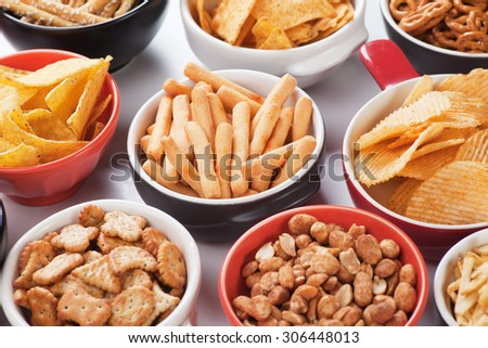 Grissini sticks, potato chips and other salty snacks - stock photo