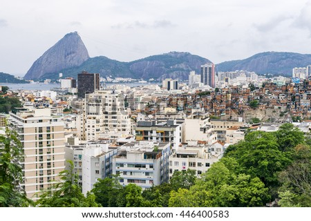 Gritty urban overlook of the Rio de Janeiro city skyline with Sugarloaf Mountain looming over residential apartments and a nearby favela adjacent to the hillside Santa Teresa neighborhood - stock photo