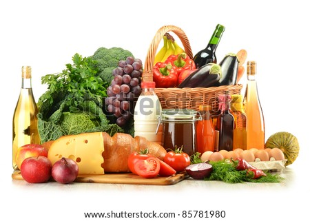 Groceries in wicker basket including vegetables, fruits, bakery and dairy products and wine isolated on white. Balanced diet - stock photo