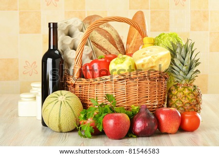 Groceries in wicker basket on kitchen table including vegetables, fruits, bakery and dairy products and wine - stock photo