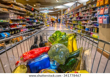 Grocery cart at a supermarket aisle filled up with food products seen from the customers point of view - stock photo
