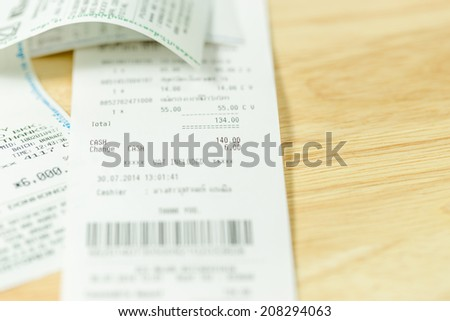 Grocery shopping list on a till roll printout on wood board background - stock photo