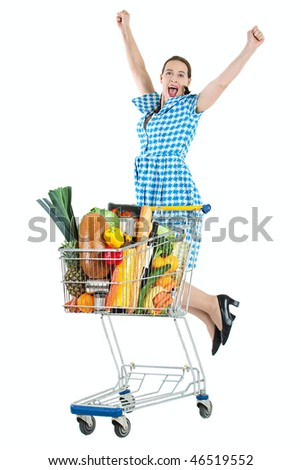 Grocery shopping with a happy young woman and a trolly full of fresh groceries. - stock photo