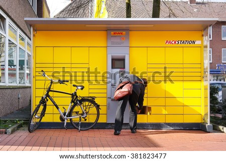 GRONAU, GERMANY - FEBRUARY 23, 2016: Customer pick-up his mail at a DHL automated parcel collection point. DHL is a trade name of Deutsche Post DHL, a German courier company and world's largest. - stock photo