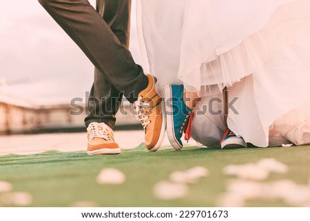groom and bride in plimsolls on green carpet - stock photo