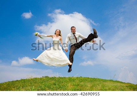 Groom and bride jumping against backdrop a sky and trees. In all growth. - stock photo
