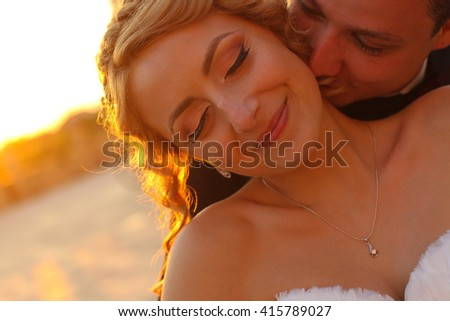 groom and bride kissing at sunset - stock photo