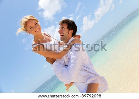 Groom and bride laughing on a sandy beach - stock photo