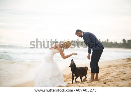 groom and bride playing on the beach on a tropical island - stock photo