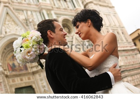groom and bride posing in front of a church - stock photo