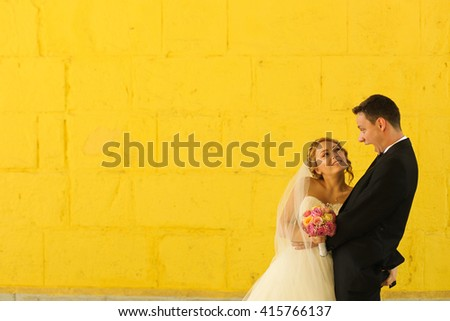 groom and bride posing with a yellow wall in background - stock photo
