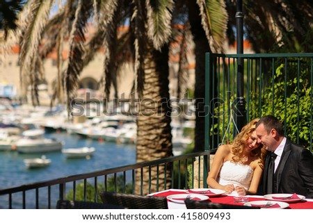 groom and bride sitting in an open air restaurant by the sea - stock photo