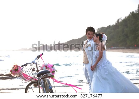 groom and bride standing on sea beach beside old classic bicycle use for wedding topic - stock photo