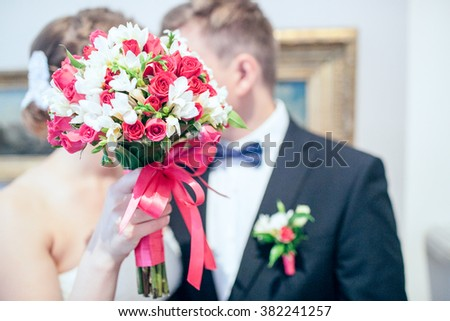 Groom and bride together with flowers - stock photo