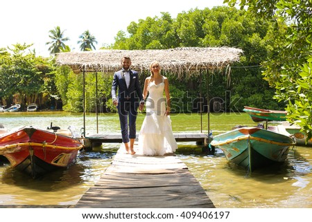 groom and bride walking on a deck on a tropical island - stock photo