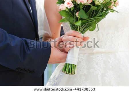 Groom and bride (young couple) holding bouquet of flowers in hands - stock photo