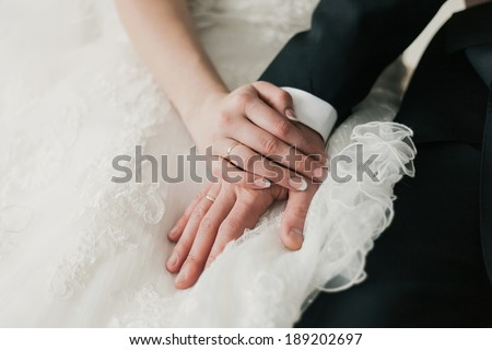 Groom and brides hands with rings, closeup view - stock photo