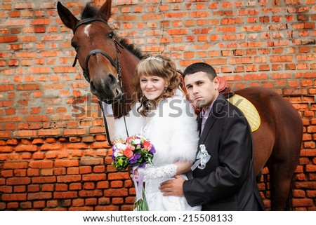 groom and the bride during walk in their wedding day against a brown horse and old brick wall - stock photo
