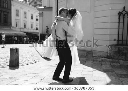 groom carries his bride in his arms through the old town - stock photo