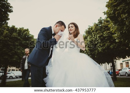 Groom cries in bride's dress while she looks shoked - stock photo