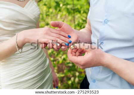 groom dresses bride golden wedding ring at the ceremony. - stock photo