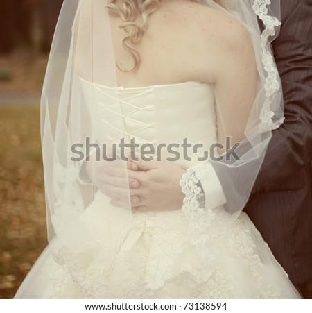 groom embracing his bride - stock photo