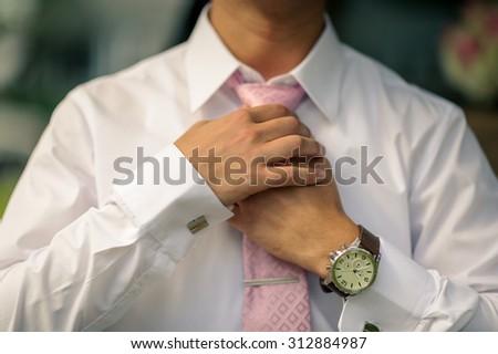 Groom fixing tie - stock photo