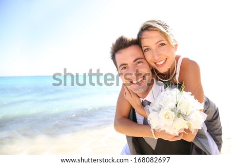 Groom giving piggyback ride to his bride - stock photo