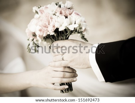 Groom handing wedding bouquet to bride  - stock photo