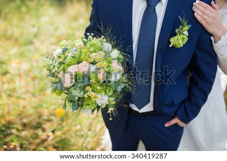 groom hold wedding bouquet in his hand - stock photo