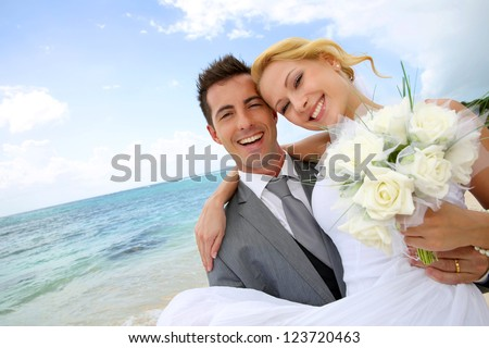Groom holding bride in his arms at the beach - stock photo